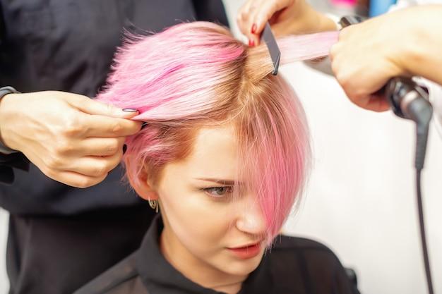 美容師は美容院でヘアーアイロンで若い女性のピンクの髪をストレートします。