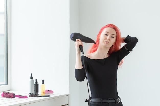 Парикмахер, стиль, люди концепции - id женщины сушат ее окрашенные волосы феном.