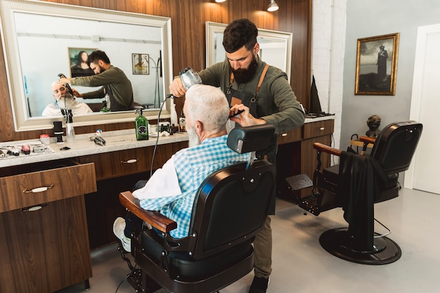 Hairdresser styling beard to aged client in salon