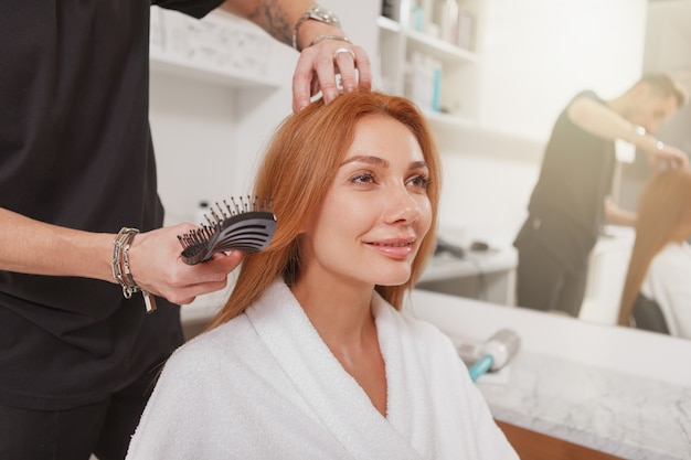 Hairdresser styling hair of a female client