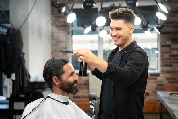 Hairdresser styling hair medium shot