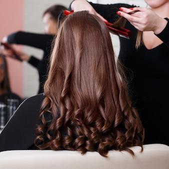 Парикмахер укладывает длинные вьющиеся волосы
