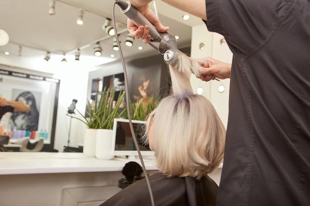 Парикмахер укладывает волосы молодой женщины в салоне красоты