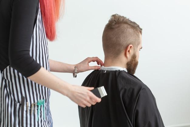 Парикмахер, стилист и концепция парикмахерской - парикмахер молодой женщины собирается стричь мужские волосы