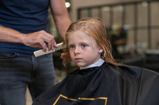 Hairdresser stylist combing boy's hair before cutting