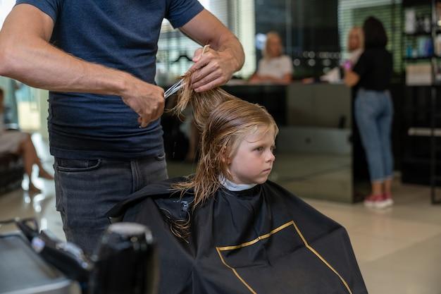 Парикмахер-стилист стрижет мальчику волосы ножницами