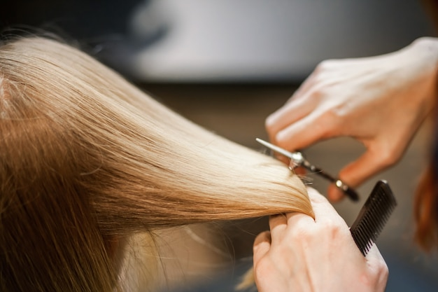 미용사 스타일리스트가 살롱에서 소녀의 머리카락을 가위로 자릅니다.