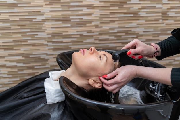 シンクの上の美容師-スタイリストが女の子の髪を洗う