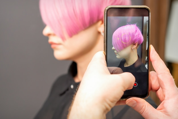 The hairdresser takes pictures of the short pink hairstyle of a young woman on the smartphone