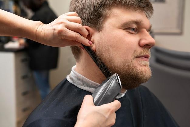 クライアントのあごひげの世話をする美容師
