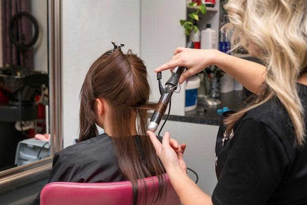 살롱에서 고객의 머리카락을 돌보는 미용사