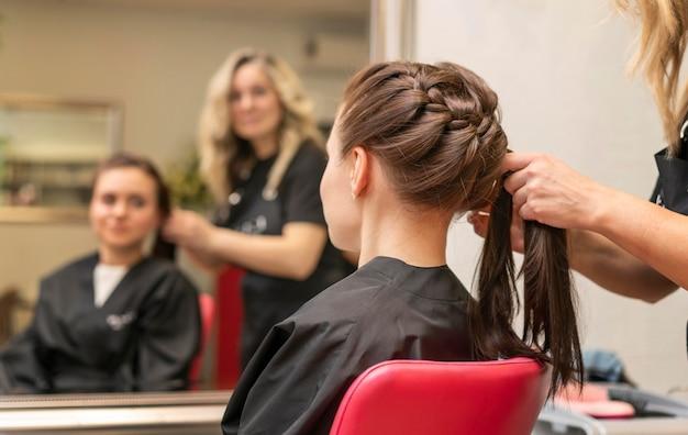 屋内でクライアントの髪の世話をする美容師