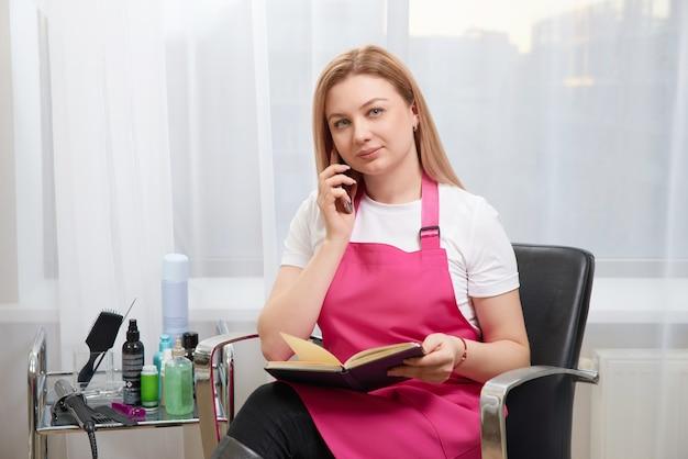 Парикмахер разговаривает с клиентом по телефону, назначая встречу