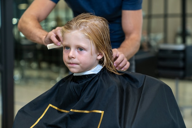 The hairdresser thoroughly combs the boy's hair before cutting it