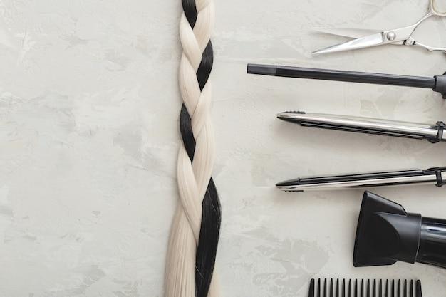 美容ツールとヘアブレード。はさみ、くし、灰色の背景にヘアアイロン