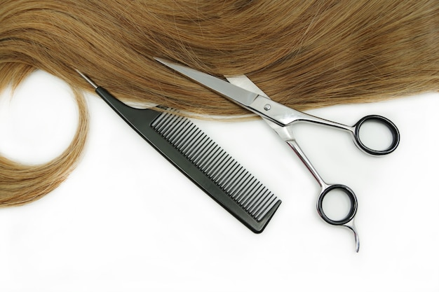 Hairdresser tools and curl of hair isolated on white