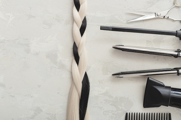 Hairdresser tools and hair braid. scissors, combs, hair iron on gray background