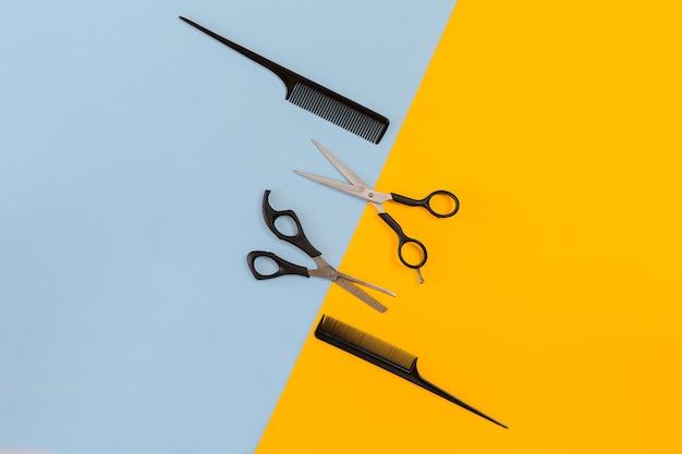 Инструменты парикмахера на синем и желтом фоне с копией пространства, вид сверху, плоская планировка. расческа, ножницы. натюрморт.