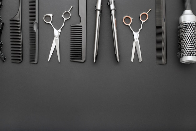 Hairdresser tools scissors combs hair iron, black frame with copy space. beauty hairdresser services