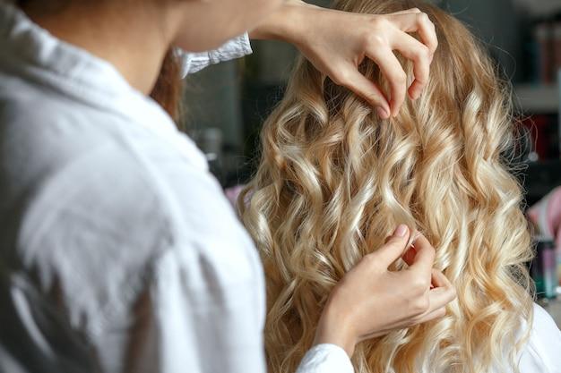 ビューティーサロンでスタイリングした後、美しいクライアントの髪に触れる美容師。クローズアップショット