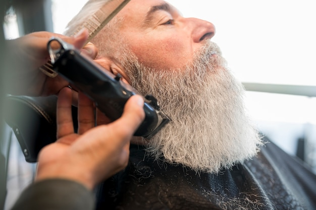 Hairdresser trimming beard to aged man