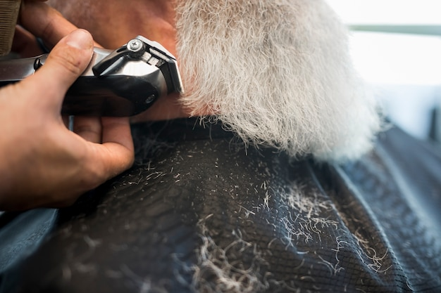 Hairdresser trimming beard with electric razor to client