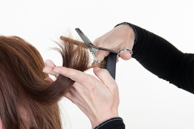 ハサミで茶色の髪をトリミングする美容師