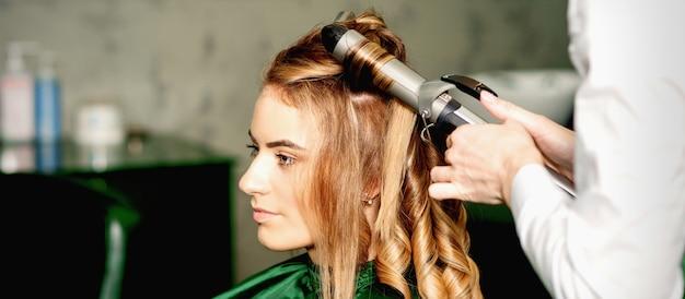 Парикмахер с помощью щипцов для завивки завивает длинные каштановые волосы на молодой кавказской девушке в салоне красоты