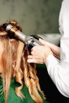 Парикмахер с помощью щипцов для завивки завивает длинные каштановые волосы на молодой кавказской девушке в салоне красоты.