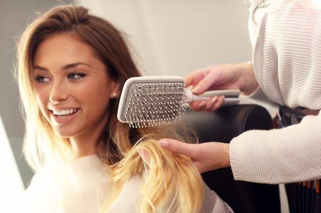 Hairdresser using hair brush in studio