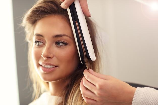 Парикмахер, используя выпрямитель для волос в студии