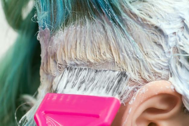 Парикмахер, используя розовую щетку, наносит краску клиентке с изумрудным цветом волос во время процесса обесцвечивания корней волос