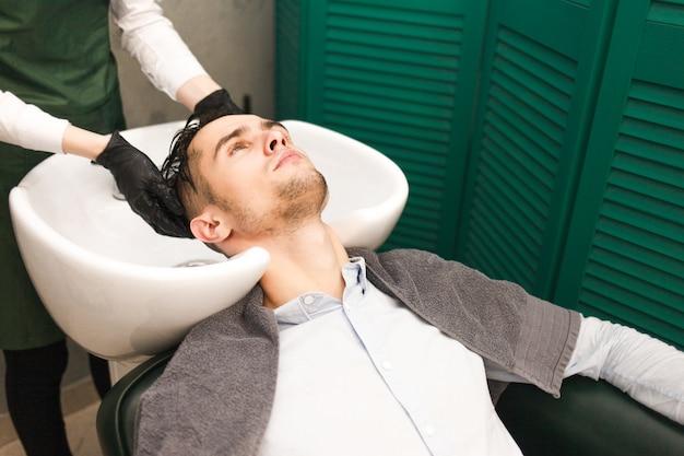 Парикмахер моет волосы клиента перед стрижкой. серьезный красавец моет голову в салоне красоты