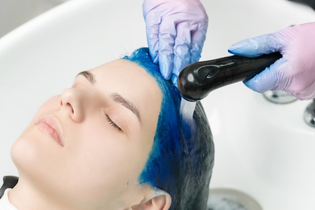 Hairdresser washes client's head with sapphire hair color after hair coloring process. washing hair with shampoo of young woman in sink with special shower in beauty salon.