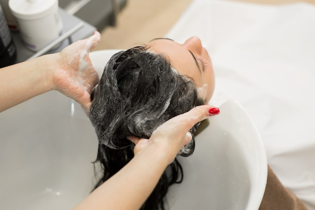 Парикмахер моет волосы шампунем и массирует голову женщины