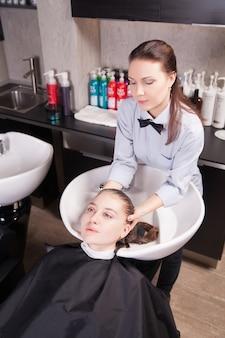 サロンで女性のブロンドの髪を洗う美容師