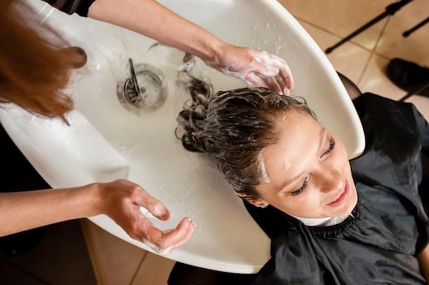 Парикмахер моет волосы клиента Premium Фотографии