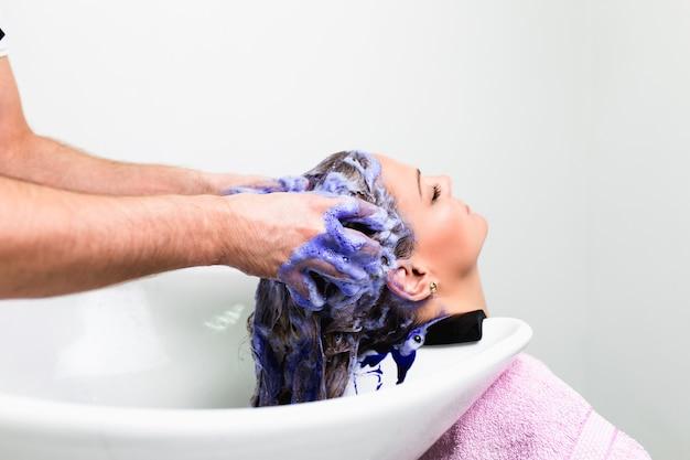 헤어 살롱에서 아름 다운 여자의 머리를 세척하는 미용사
