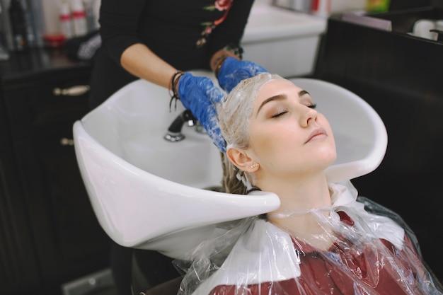 Parrucchiere che lava la testa della donna