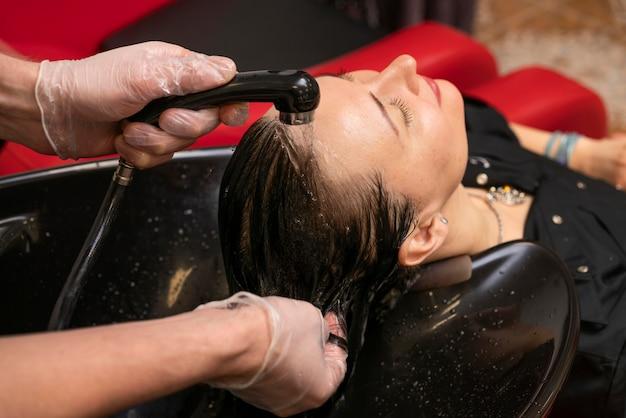 Parrucchiere che lava i capelli di una donna
