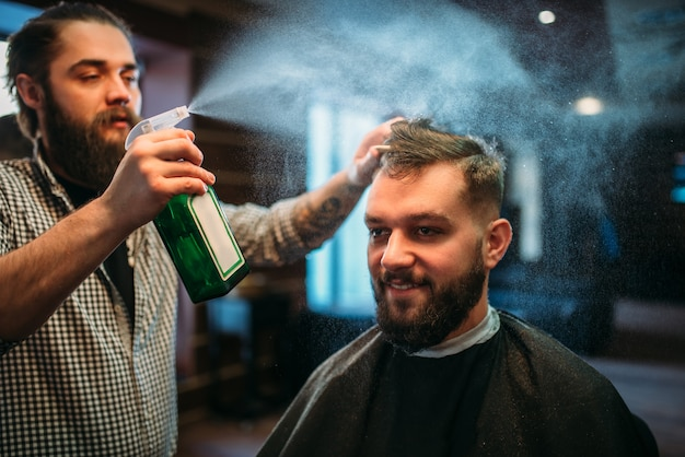 Hairdresser water with spray hair of the client man in black salon cape.