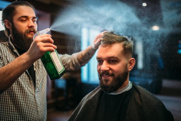 Парикмахерская вода с распылением волос клиента в черном салоне-накидке.