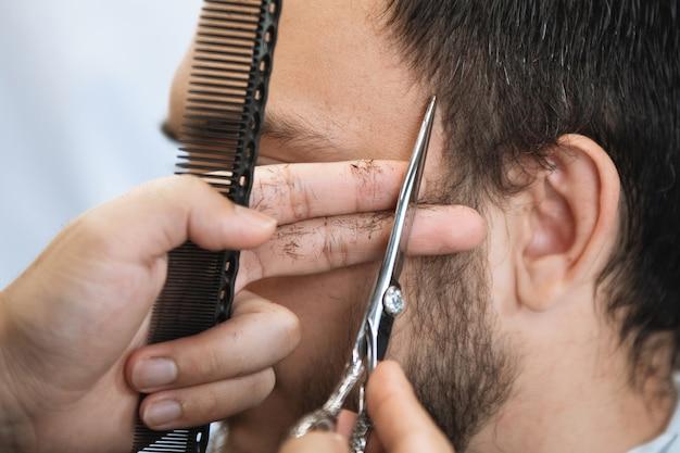 Парикмахер с расческой и ножницами стрижет бородатого мужчину в кресле в салоне парикмахерской