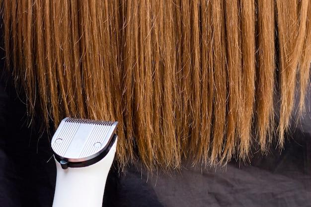 Парикмахер с машиной для волос. срезание секущихся кончиков волос машинкой для стрижки. крупным планом. обрезка секущихся кончиков