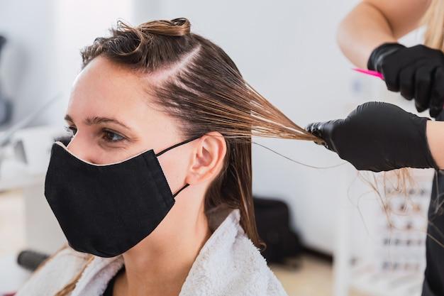 Парикмахер с маской для лица и перчатками, наносящими краску клиенту