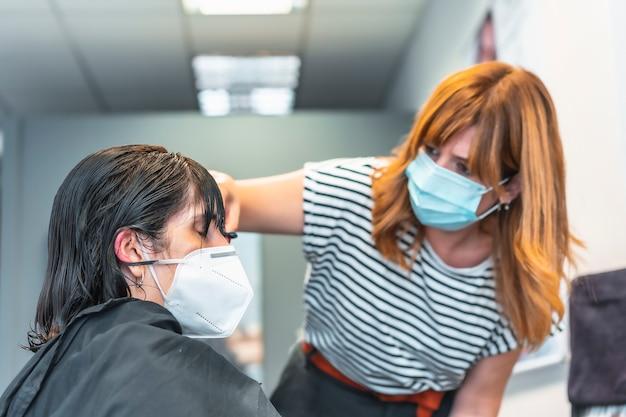 フェイスマスクカットと美容師は、マスクでクライアントに前髪。 covid-19パンデミックにおける美容院の安全対策。新しい正常、コロナウイルス、社会的距離