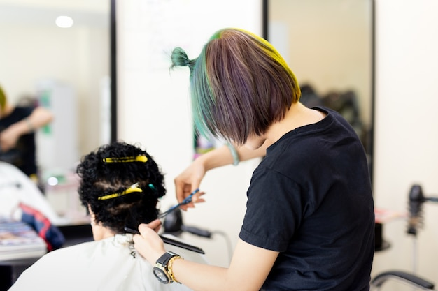 Hairdresser with fashion colourful hair style cutting old lady is hair