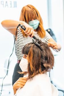 ウェーブのかかった髪型を始める、マスクとクライアントを備えた美容師。 covid-19パンデミックにおける美容院のセキュリティ対策を再開。新しい正常、コロナウイルス、社会的距離
