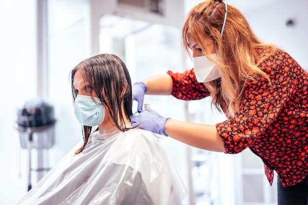 Парикмахер с маской и перчатки, подстригающие волосы клиента. открытие с мерами безопасности для парикмахеров в пандемии covid-19