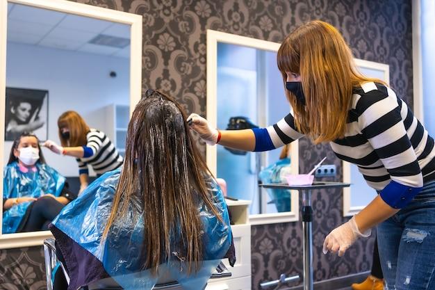 Парикмахер с маской наносит краситель перед зеркалом клиенту с маской. открытие с мерами безопасности парикмахерских в пандемии covid-19, коронавируса